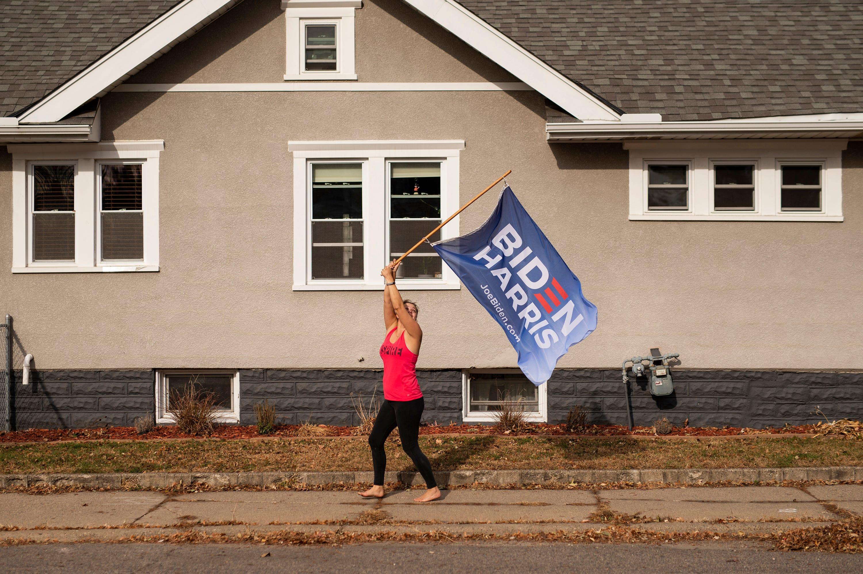 A woman carries a Biden Harris flag as people celebrate in Minneapolis.