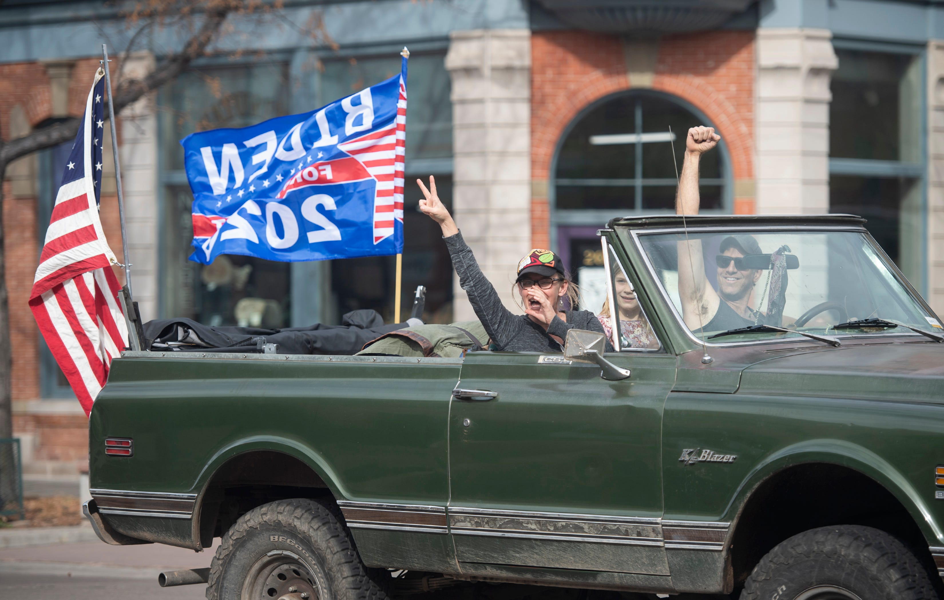 People cheer from their vehicle after Democratic candidate Joe Biden wins the 2020 presidential election in Old Town Fort Collins, Colo.