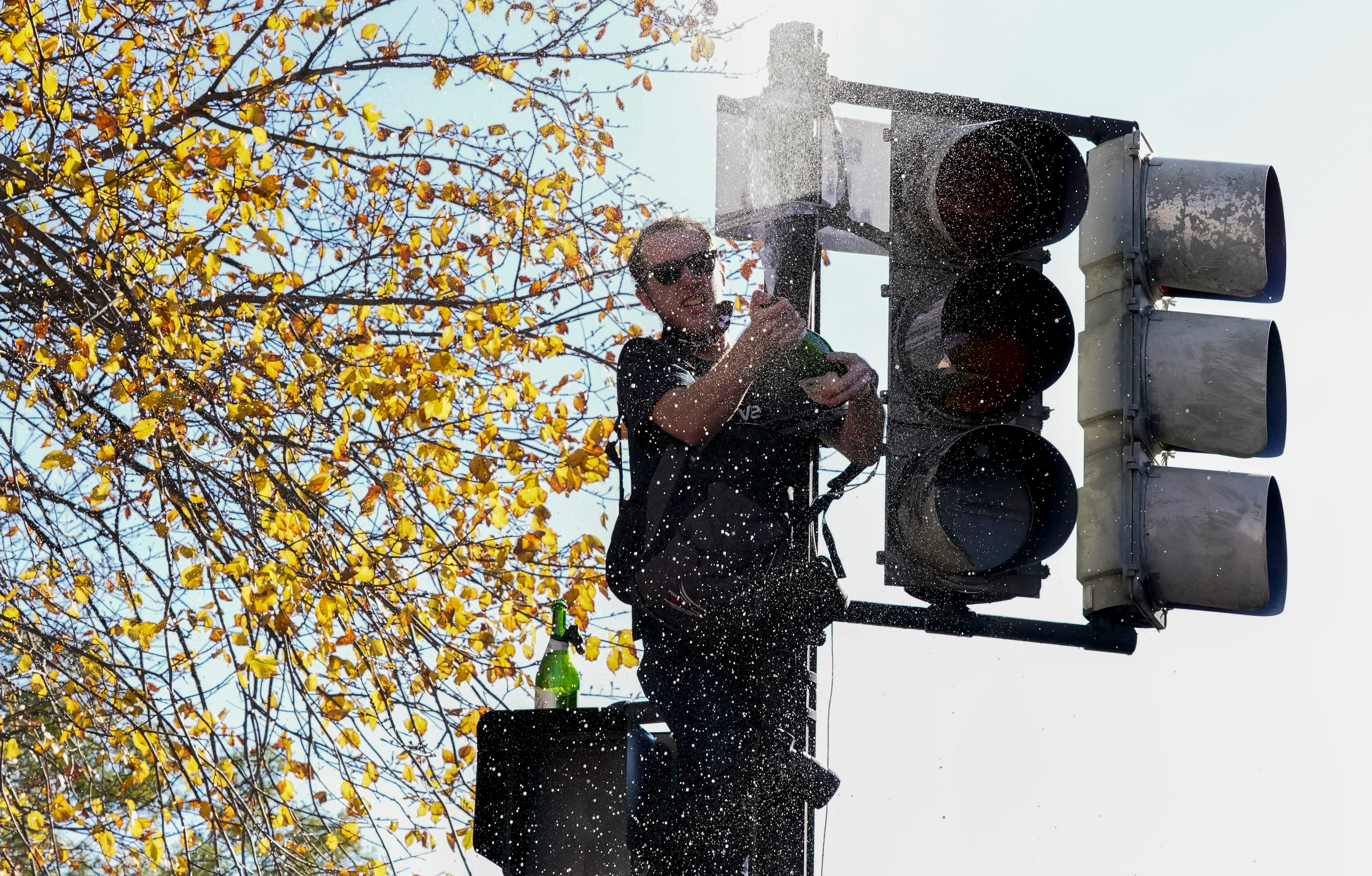 A man sprays champagne from atop a traffic light in Black Lives Matter Plaza in Washington, D.C.