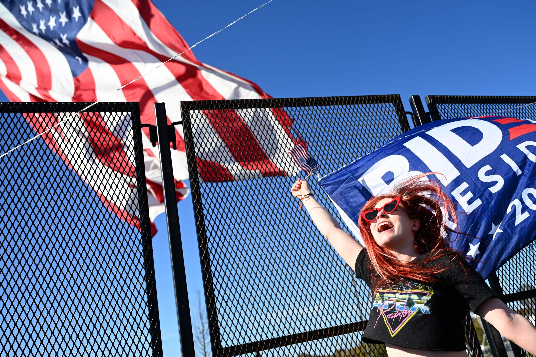 A supporters of President-elect Joe Biden waves a flag in celebration in Wilmington, Delaware.