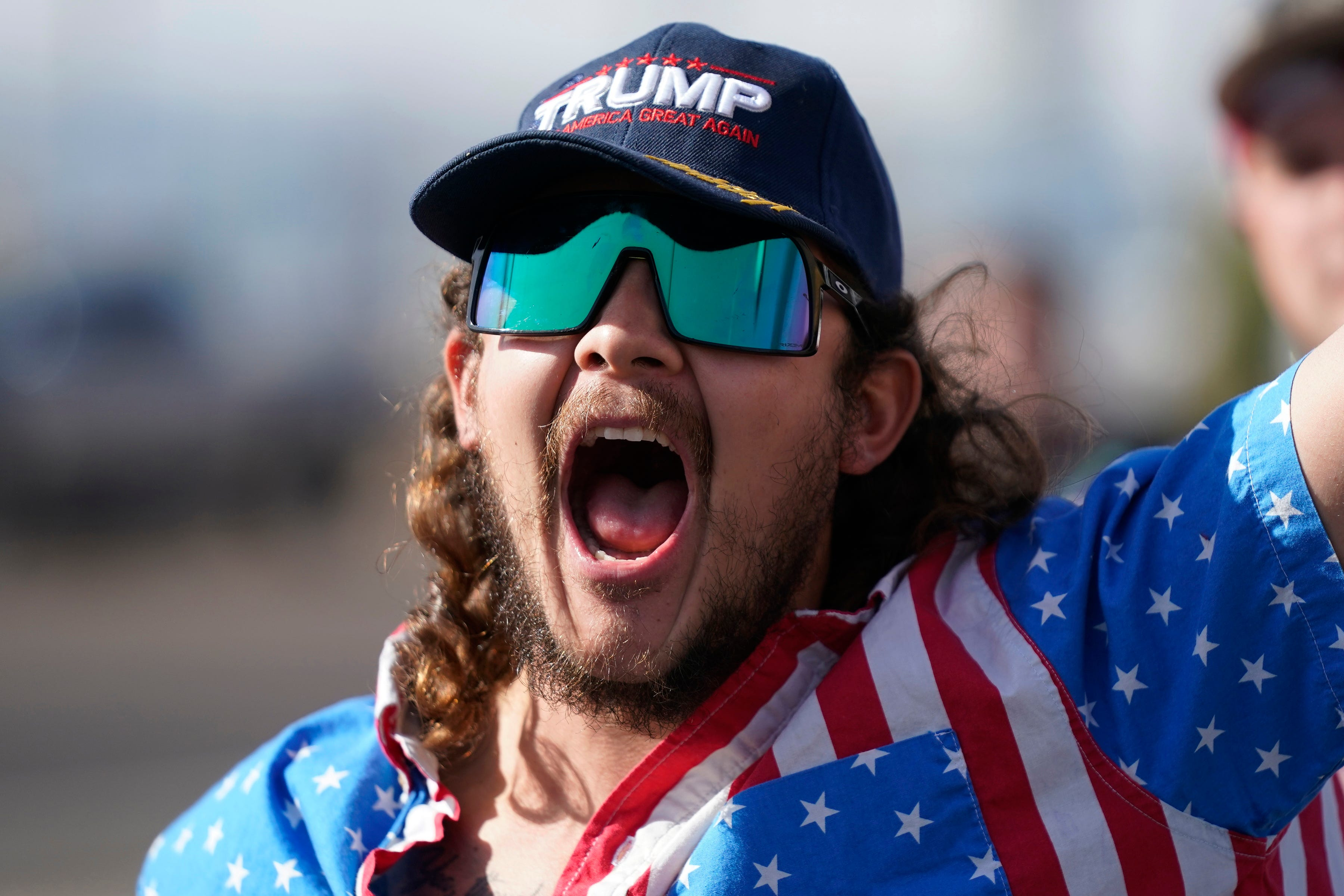 A supporter of President Donald Trump shouts during a rally outside the Maricopa County Recorder's Office in Phoenix.