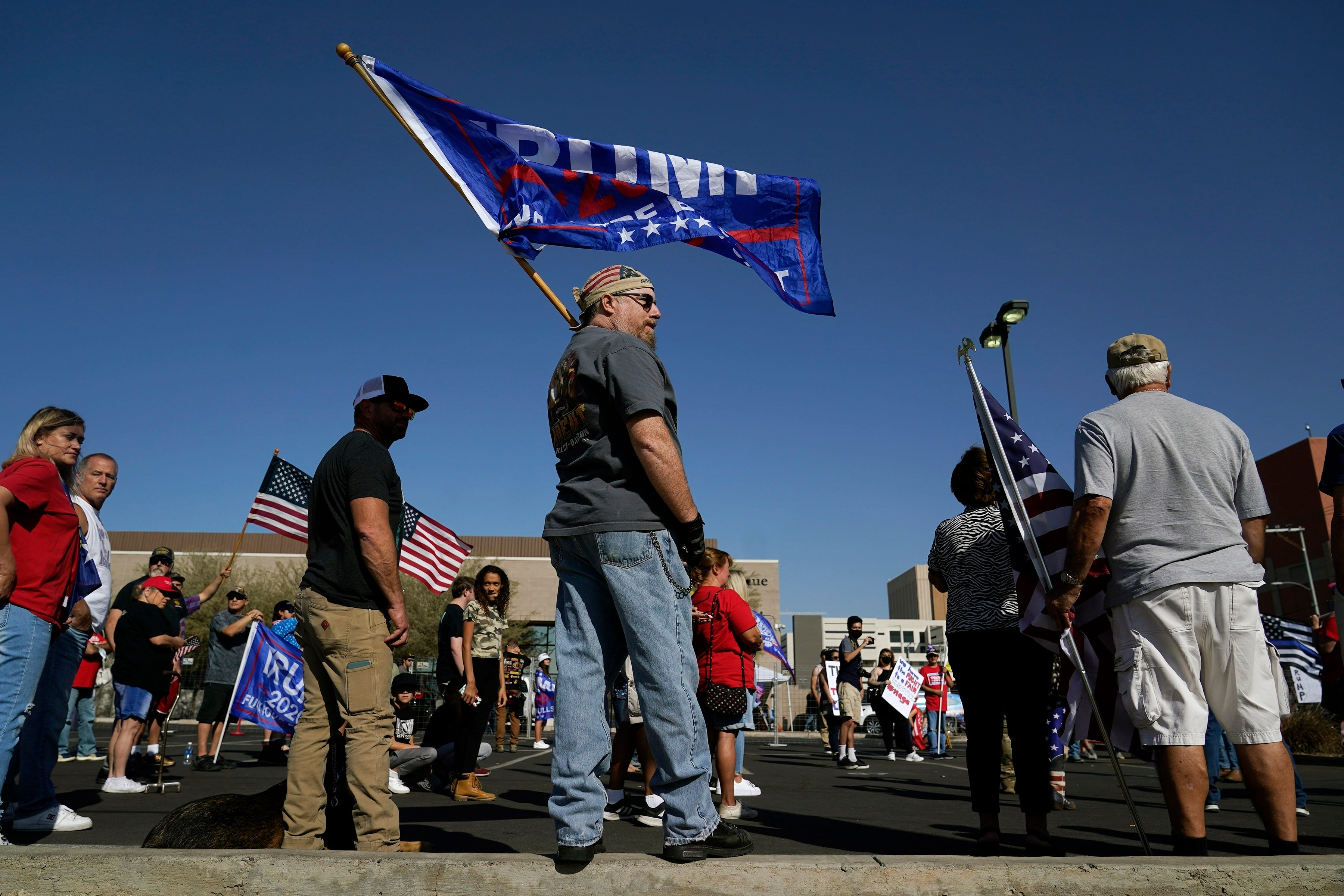 A man holding a Trump flag rallies outside the Maricopa County Recorder's Office in Phoenix.