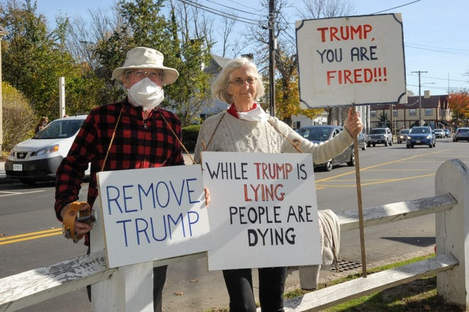Earle Barnhart and his wife, Hilda Maingay, take part in what is likely the final Move to Remove rally on the Falmouth Village Green on Saturday. The group has gathered in protest of President Donald Trump for the past 168 weeks.
