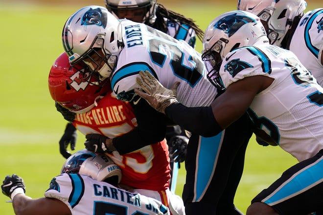 Carolina Panthers cornerback Corn Elder, center, and teammates tackle Kansas City Chiefs running back Clyde Edwards-Helaire.