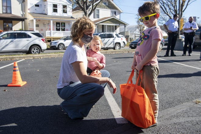"""Milo Meier, 4, stands proudly with his new orange bag of science experiments, as his mother Megan Meier and 1-year-old sister Quinn Meier stand beside him at Avondale Elementary School on Saturday. CoverMyMeds and COSI teamed up to distribute 500 human physiology themed """"learning lunchboxes"""" to students in the Franklinton and Hilltop area."""
