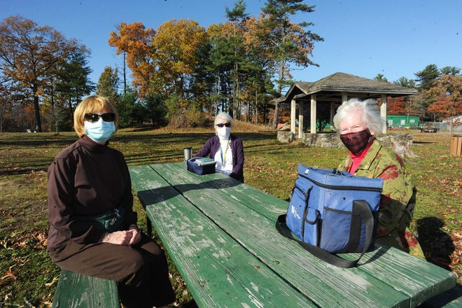 From left, Kitty Clapp, Joann Wyner and Jane Durna, of Brockton, have lunch at a picnic table at D.W. Field Park in Brockton, Friday, Nov. 6, 2020. A new mask requirement went into effect in Massachusetts the same day, requiring people to wear face masks in public spaces, too.