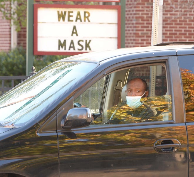 """A man wearing a face mask drives past the Brockton Council on Aging, which has """"WEAR A MASK"""" on its sign, Friday, Nov. 6, 2020."""
