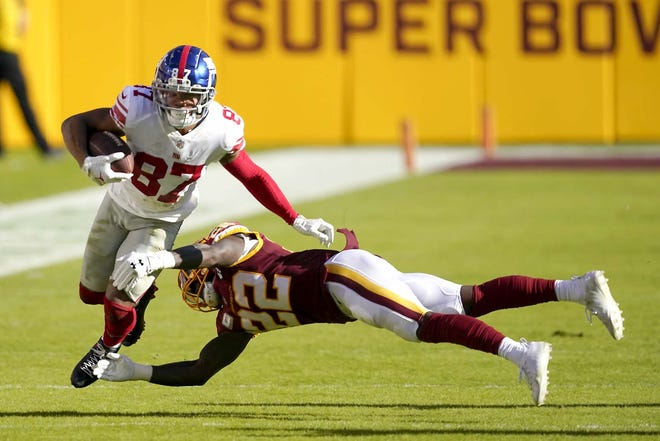 New York Giants wide receiver Sterling Shepard (87) tries to runs past Washington Football Team safety Deshazor Everett (22) during the first half of Sunday's game in Landover, Maryland.