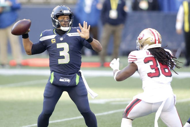 Seattle Seahawks quarterback Russell Wilson (left) throws a touchdown pass to wide receiver DK Metcalf as San Francisco 49ers safety Marcell Harris pressures him during a Nov. 1 game in Seattle.