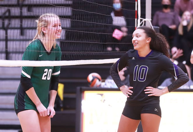 West Burlington's Syndey Marlow (Black Team) and Burlington's Madison Bunton (Pink Team have a laugh at the net before the next serve Saturday at Mediapolis.