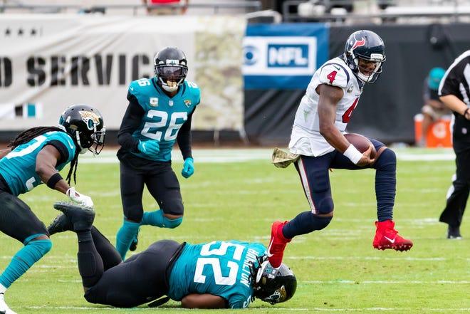 Houston Texans quarterback Deshaun Watson (4) leaps over Jacksonville Jaguars defensive tackle DaVon Hamilton (52) in the fourth quarter.