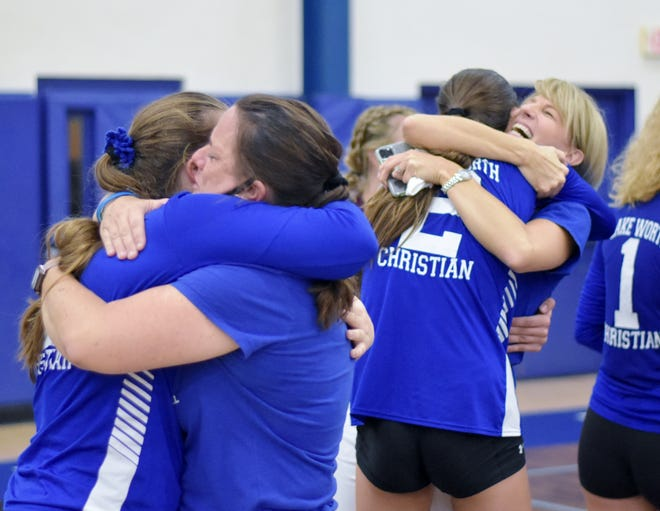 Lake Worth Christian players celebrate the dramatic five-set win against First Baptist. There were tears of joy and smiles as the Defenders secured a return to the state title game.