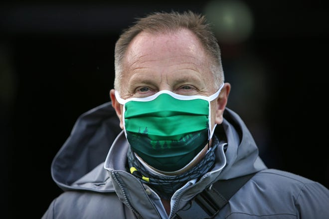 A masked Rob Mullens watches from the sideline as Oregon plays Stanford in a Nov. 7 football game at Autzen Stadium.