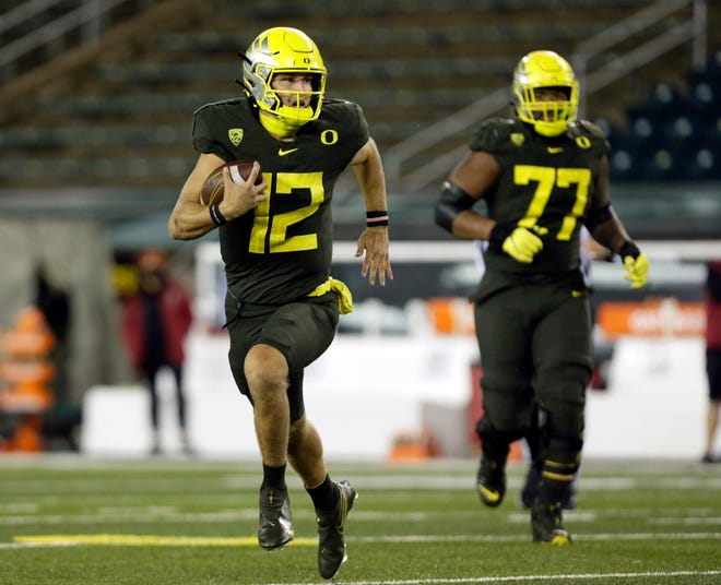Oregon quarterback Tyler Shough (12) scrambles for a big gain during last Saturday's win over Stanford while tackle George Moore looks on.