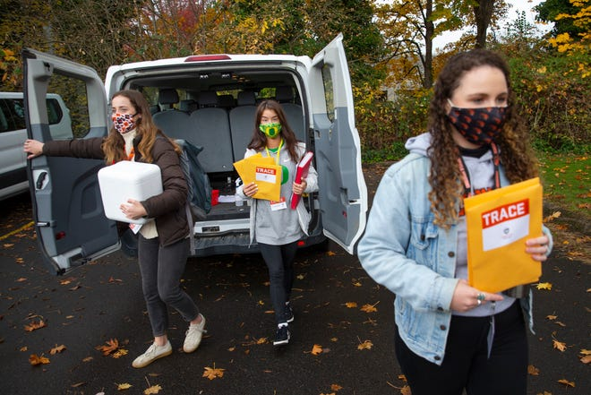 Kate Boyd, left, Denielle Reynolds and Sahlea Tubbeh bring COVID-19 tests samples back to their staging area in Eugene.