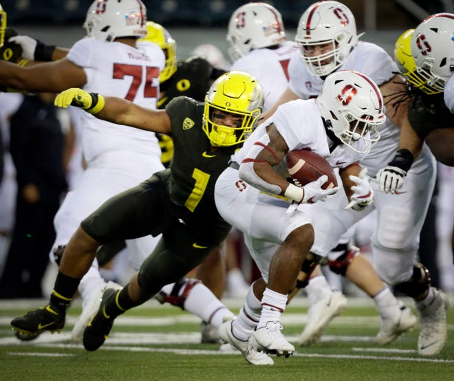 Oregon linebacker Noah Sewell (1) tackles Stanford running back Nathaniel Peat for a loss during the Ducks' 35-14 win over the Cardinal on Nov. 7 at Autzen Stadium.