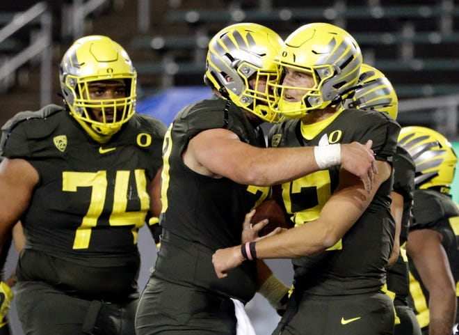 Oregon quarterback Tyler Shough (12) celebrates with his offensive line after rushing for a third-quarter touchdown in last week's 35-14 win over Stanford at Autzen Stadium.