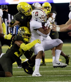 Oregon linebackers Dru Mathis (bottom) and Isaac Slade-Matautia (41)  stop Stanford running back Justus Woods (21) during the second quarter of the Ducks' 35-14 win over the Cardinal on Nov. 7 at Autzen Stadium.