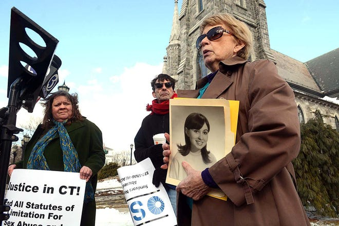 Gail Howard of Redding holds a photo of herself at age 17, when she said she was abused by a priest in Chicago, as she participates in a February 2019 protest outside the Cathedral of St. Patrick in Norwich.