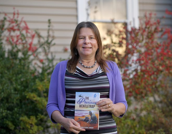 "Deborah Snyder outside her Rutland home with her first novel, ""The Precious Wentletrap""."