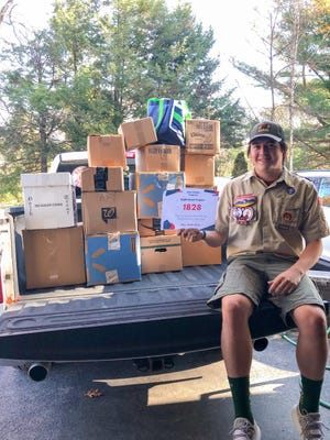 Jason Weldon with boxes of glasses donated through his Eagle Scout project.