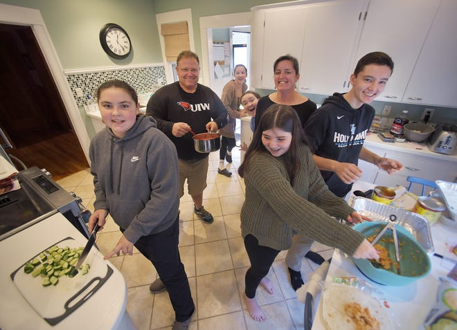 From left, Emma O'Connor, 12, her father Dennis, neighbor Roisin O'Malley, 12, Claire O'Connor, 14, her mother Mary O'Connor, Terry O'Connor, 12, and friend Brigid, 12, pause for a photo in the controlled chaos of the kitchen at their home in Worcester. The O'Connors cook at home on Sundays and serve the food to homeless people on Sunday nights at Ascension Church.