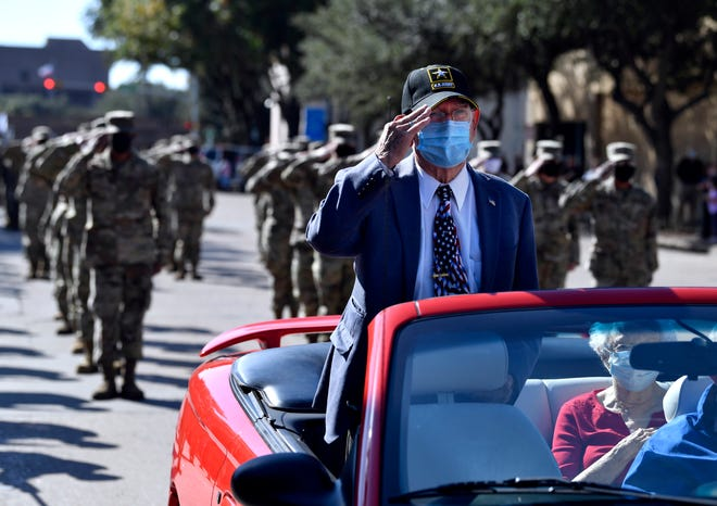 Retired U.S. Army Gen. Robert Jerry Strader salutes during the playing of the national anthem at the start of Saturday's Veterans Day parade in downtown Abilene. Strader was this year's parade grand marshal.