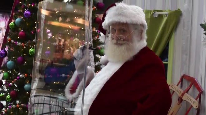 Santa Claus wears a face mask and sits behind a plastic shield