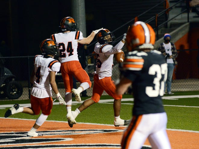Deontae Brandon celebrates with teammates Kigenn Millender, left, and Kurtis Varian after scoring a touchdown during the second quarter of Ridgewood's 17-7 win against host Ironton in the Division V, Region 19 championship game at Tanks Memorial Stadium. Brandon's score tied the game at 7.