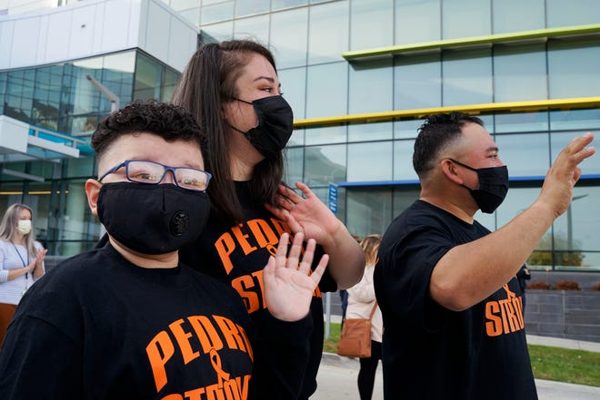 Pedro Martinez, 11, and his parents, Leticia and Juan Martinez, watch cars filled with family and friends drive by after he rang the bell to signify him recovering from cancer outside the Michigan Children's Hospital on Nov. 6, 2020, in Detroit.