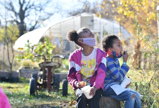 Dari kiri, Gabriella Ware, 9, dari Detroit berhenti sejenak untuk memakan donatnya untuk melihat ke atas, sementara kakaknya, John Ware II, memakan donatnya di Detroit Farm & Cider di Lawrence Street di Detroit pada 9 November 2020. Lokasi buka pada akhir pekan hingga 5 Desember. Perayaan Kwanzaa dan program sepanjang tahun sedang direncanakan.