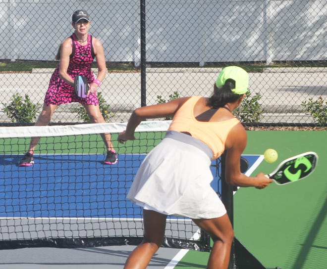 """Head pickleball instructor Mae Brown, foreground, plays a tricky """"dink"""" shot against opponent Jen McCalla in an exhibition match."""