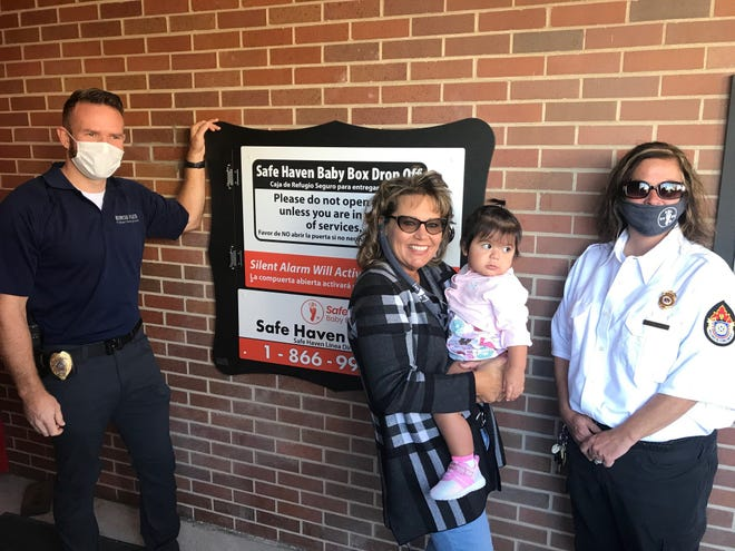 A ceremony on Saturday marked the dedication of the new Safe Haven baby box - allowing mothers to safely and anonymously surrender custody of their infants — at the downtown Muncie fire station. From left are Kris Swanson, city police officer and a member of Prevent Child Abuse Delaware County; Safe Haven founder Monica Kelsey; Grace, a child who was placed in a Safe Haven box in Hammond as a newborn, and Rachel Clark, of the Muncie Fire Department's ambulance service.