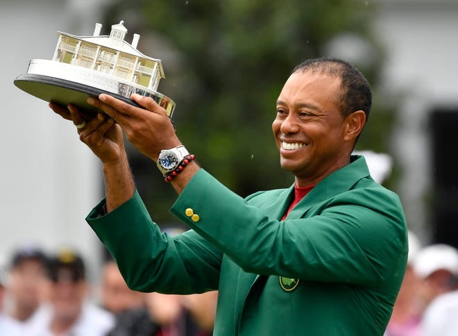 Tiger Woods celebrates with the green jacket and trophy after winning The Masters golf tournament at Augusta National Golf Club.