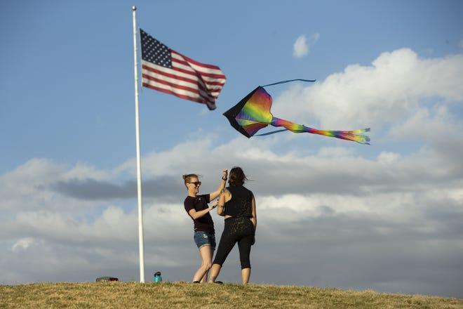 Amanda Thompson (left) and Manuela Arboleda (right) fly a kite on a windy day at Indian Steele Park in Phoenix, Ariz., on Nov. 7, 2020.