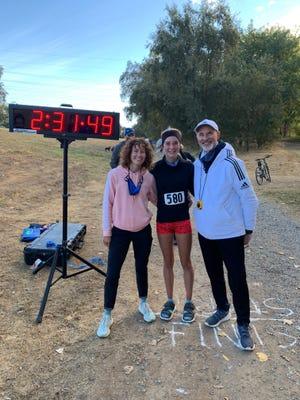 Nevada freshman Tierney Wolfgram, center, broke the Women's American Junior marathon record on Saturday.  Coaches Kirk Elias and Emkay Sullivan are at her sides.