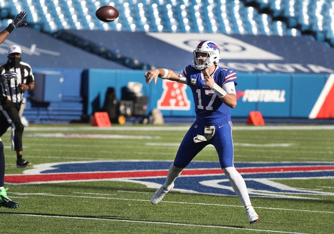 Bills quarterback Josh Allen makes an off balance throw against the Seahawks.  Allen was 31 of 38 for 415 yards and three touchdowns.