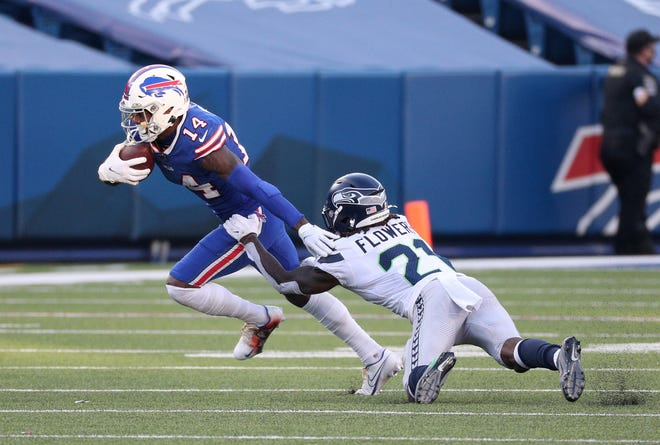 Bills receiver Stefon Diggs tries to slip a tackle by Seahawks Tre Flowers.  Diggs caught nine passes for 118-yards.