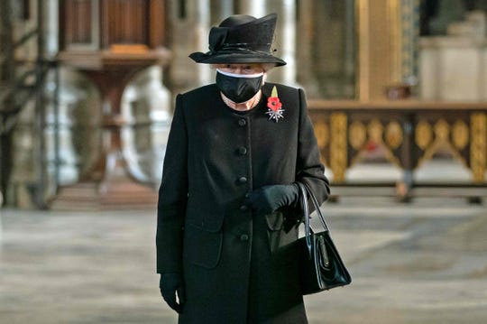 Britain's Queen Elizabeth II looks at the grave of the Unknown Warrior during a service to mark the centenary of the burial of the Unknown Warrior ahead of Remembrance Sunday at Westminster Abbey in London on November 4, 2020.