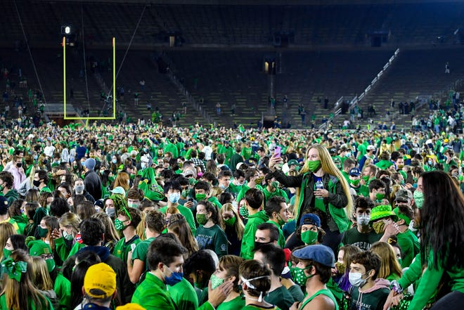 Fans storm the field after the Notre Dame Fighting Irish defeated the Clemson Tigers in double overtime.