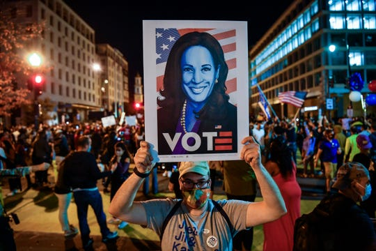 People gather near the White House along the Black Lives Matter Plaza late in the evening on Nov. 7, 2020, after Democrat Joe Biden defeated President Donald Trump to become 46th president of the United States.