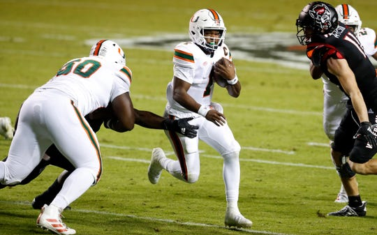Miami (Fla.) quarterback D'Eriq King (1) runs past North Carolina State's defense at Carter-Finley Stadium in Raleigh, N.C.