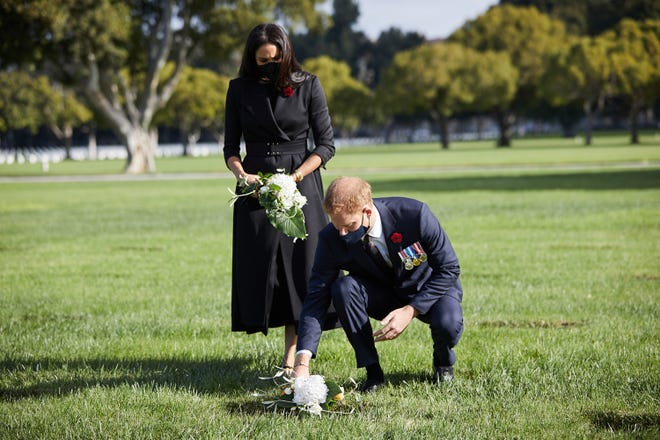 Prince Harry and Duchess Meghan of Sussex put flowers on the grave of war dead at Los Angeles National Cemetery on Nov. 8, 2020, Remembrance Sunday in the United Kingdom.