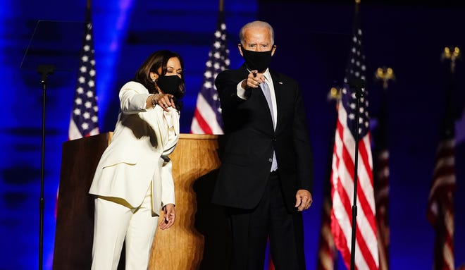 Vice President-elect Kamala Harris, left, and President-elect Joe Biden point to supporters during a celebratory moment between their two speeches Saturday at an outdoor gathering in Wilmington, Delaware.