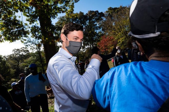 Georgia Democratic candidate for U.S. Senate Jon Ossoff interacts with a supporter as he rallies support for a runoff against Republican candidate Sen. David Perdue, during a meeting in Grant Park, on Friday in Atlanta.