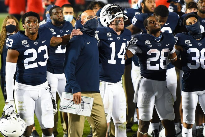 Penn State coach James Franklin stands with quarterback Sean Clifford (14) and other players during the playing of the alma mater following the loss against Maryland.