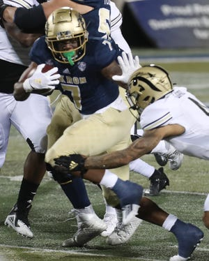 Akron's Teon Dollard wards off a Western Michigan defender on a carry Wednesday in Akron.