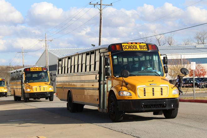 Bartlesville Public School buses leave the high school Monday afternoon to take students home.