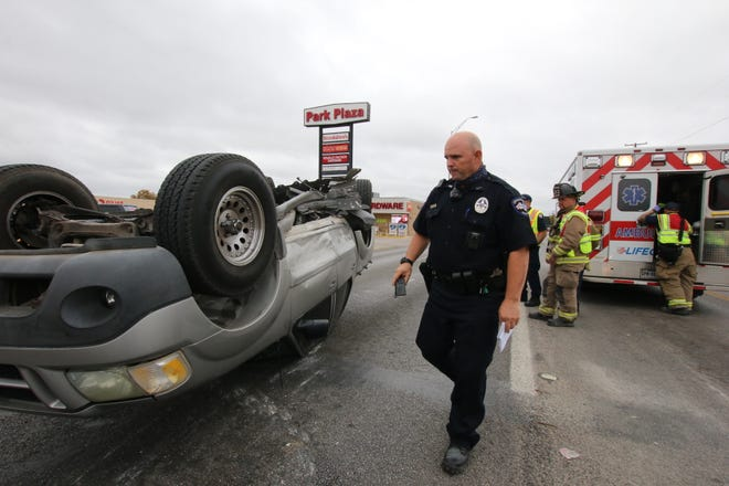Brownwood officer James Wells walks near an overturned Ford Explorer on Austin Avenue near the Coggin Avnue  intersection after a two-vehicle collision Monday morning. The male driver, who was alone in the Explorer, was transported via Lifeguard Ambulance. The two occupants of the other vehicle involved in the collision were not injured.