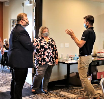 Holmes Health Commissioner Mike Derr (left) and Chamber of Commerce Director Tiffany Gerber chat with Chamber of Commerce President Kent Miller at a meeting earlier this year.